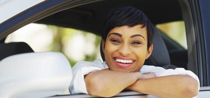 woman smiling and looking out of car window